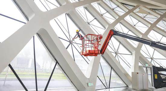 A worker installs window parts of the exhibition halls for the upcoming China International Consumer Products Expo at the Hainan International Exhibition Center on March 15. The first of such exhibitions will be held from May 7 to May 10. (GAO LIN/FOR CHINA DAILY)