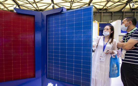 Visitors look at a solar panel during an industry expo in Shanghai.(Photo/China Daily)