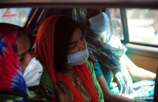 Wailing relatives of a deceased COVID-19 patient are seen in a car at Jaipur Golden Hospital in New Delhi, India, April 24, 2021. According to the health ministry, India witnessed historical high figures both in daily confirmed COVID-19 cases and new deaths on Saturday, as 346,786 more infections and 2,624 deaths were reported. The total tally has reached 16,610,481 and the death toll increased to 189,544 in the country. (Str/Xinhua)