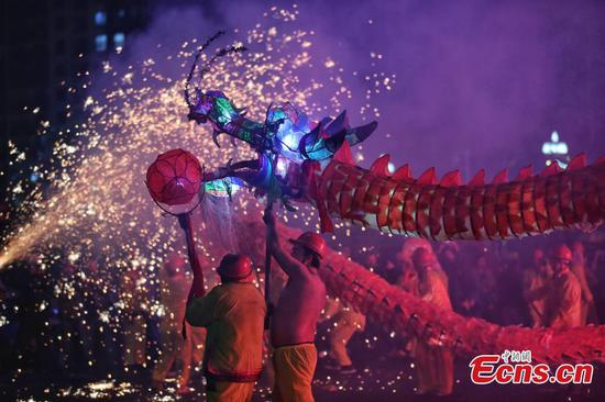 People celebrate Miao Sisters Festival with fire dragon dance