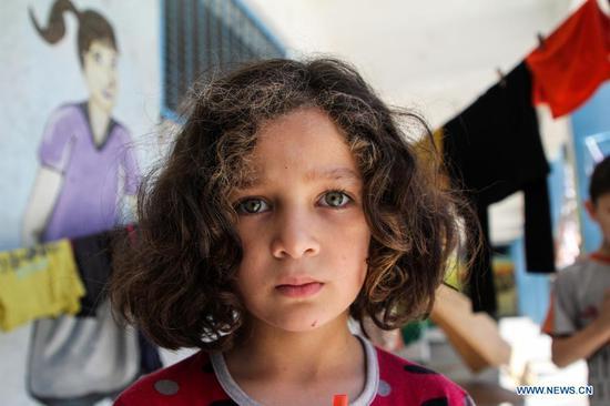 Palestinian children take refuge at school after Israeli air strikes damage homes