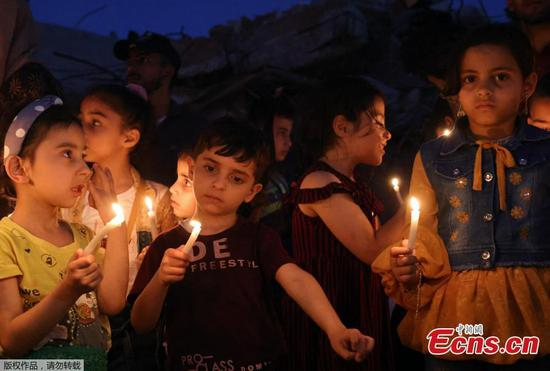 Palestinian children rally with candles on ruins