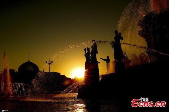 Sunset glow creates black silhouette art in VDNK
