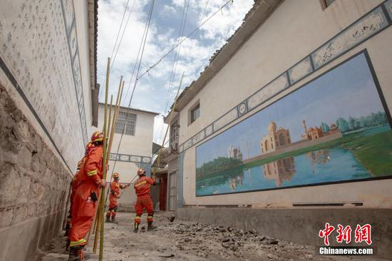 Firefighters check damaged houses after earthquake in Yunnan