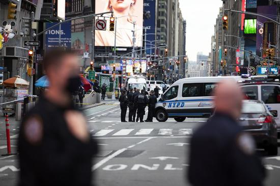 Policemen stand guard near a shooting scene in Times Square in New York, the United States, May 8, 2021. (Photo: Xinhua/Wang Ying)