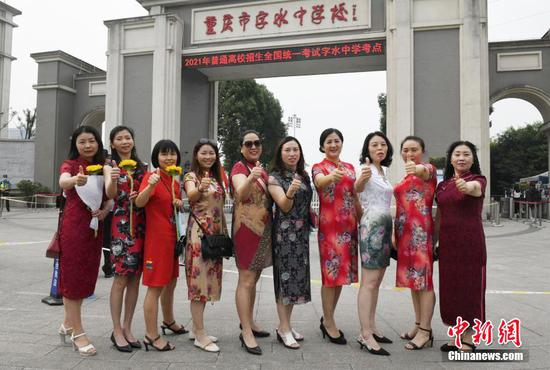 Parents of Chongqing Zishui Middle School students wear qipao to express their good luck to examinees. (Photo/China News Service)