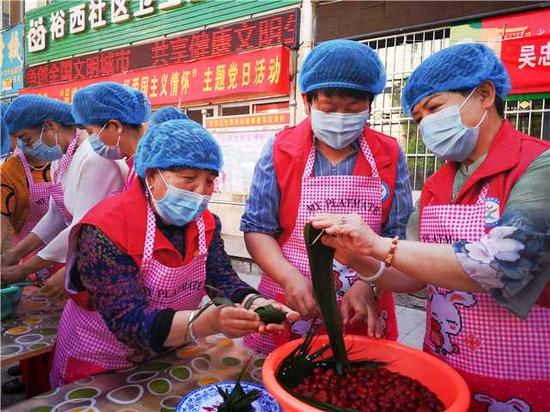 Wang Lanhua (first from left in front) makes zongzi, a festive food for the Dragon Boat Festival, with fellow community residents in Wuzhong, Ningxia Hui autonomous region, in June last year. (Photo/China Daily)