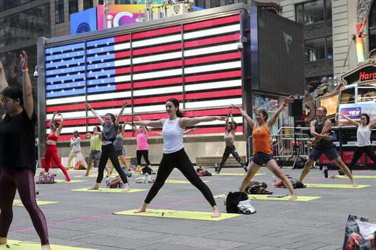 People practice yoga at Times Square to welcome summer solstice