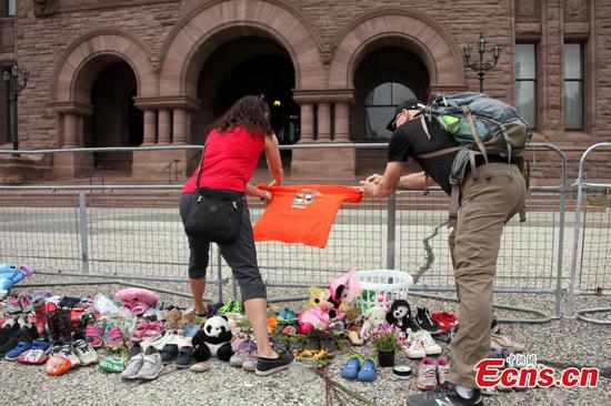"""An orange shirt printed with the message """"Every Child Matters"""" is tied to an iron fence at the front of Legislative Assembly of Ontario, Toronto, Ontario, Canada, June 2, 2021. (China News Service/Yu Ruidong)"""