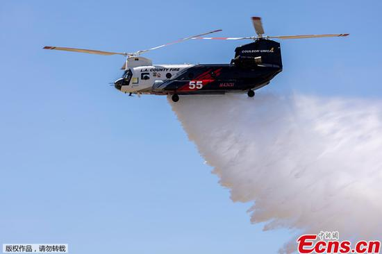 A firefighter helicopter demonstrates a water drop as officials announce a 180-day Quick Reaction Force program designed to help battle wildfires, during a media event at Joint Forces Training Base Los Alamitos in Los Alamitos, California, U.S., June 14, 2021. (photo/Agencies)