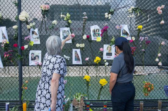 People view a makeshift memorial near the site of the residential building collapse in Miami-Dade County, Florida, the United States, on June 26, 2021. (Photo by Monica McGivern/Xinhua)