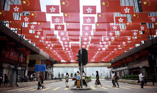 People walk past China's national flags and the flags of the Hong Kong Special Administrative Region for the celebration of 24th anniversary of Hong Kong's return to the motherland at Tsim Sha Tsui East in Hong Kong on June 29, 2021. (chinadaily.com.cn/Edmond Tang)