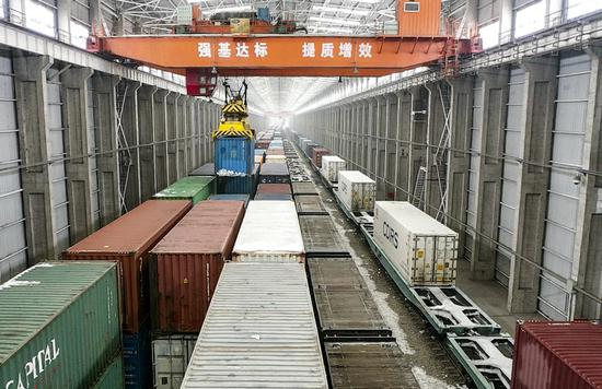 Photo taken on Feb. 7, 2021 shows hoisted containers at a warehouse in Alataw Pass of northwest China's Xinjiang Uygur Autonomous Region.(Xinhua/Ma Kai)