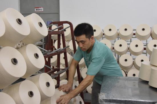 A worker packs spindles at a textile plant in Shihezi City, northwest China's Xinjiang Uygur Autonomous Region, July 7, 2021. (Xinhua/Gu Yu)