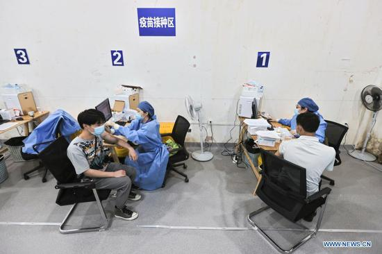 People take COVID-19 vaccines at the temporary vaccination site at Shanghai Hongqiao Railway Station in East China's Shanghai, May 29, 2021. (Photo/Xinhua)