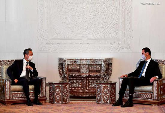 Syrian President Bashar al-Assad (R) meets with visiting Chinese State Councilor and Foreign Minister Wang Yi in Damascus, Syria, on July 17, 2021. China opposes any attempt to seek regime change in Syria and will boost the mutually beneficial cooperation with Syria for the benefit of the two peoples, Wang Yi said on Saturday. (Photo by Ammar Safarjalani/Xinhua)