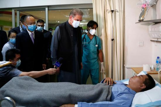 Pakistani Foreign Minister Shah Mahmood Qureshi (C) visits the injured Chinese national from the Dasu terrorist attack at the Combined Military Hospital in Rawalpindi of Pakistan's Punjab province on July 18, 2021. Pakistani Foreign Minister Shah Mahmood Qureshi on Sunday visited the injured Chinese nationals from the Dasu terrorist attack at the Combined Military Hospital in Rawalpindi near the federal capital Islamabad. The foreign minister was accompanied by Pakistani Foreign Secretary Sohail Mahmood and Chinese Ambassador to Pakistan Nong Rong. (Photo by Ahmad Kamal/Xinhua)