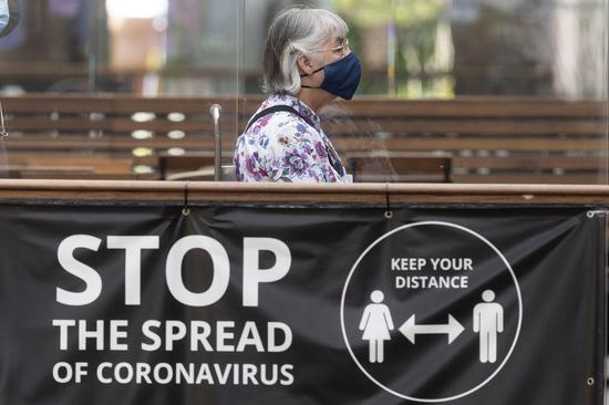 A woman wearing a face mask walks past a COVID-19 safety sign in London, Britain, on July 19, 2021. (Photo by Ray Tang/Xinhua)