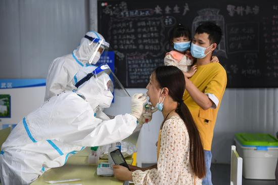 A medical worker takes a swab sample from a woman for COVID-19 test at a testing site in Nanjing, East China's Jiangsu province, July 29, 2021.(Photo/Xinhua)