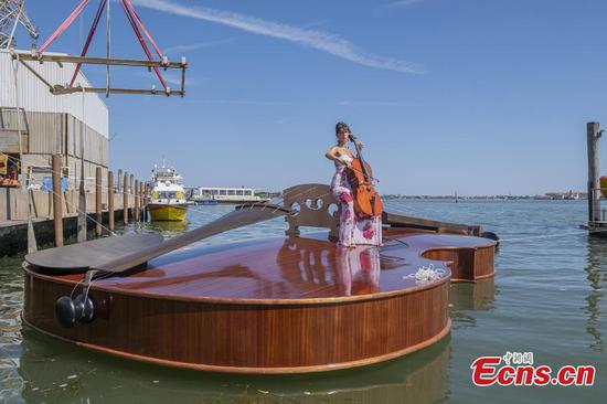 Cellist plays song on violin-shaped boat to pay homage to COVID-19 deaths