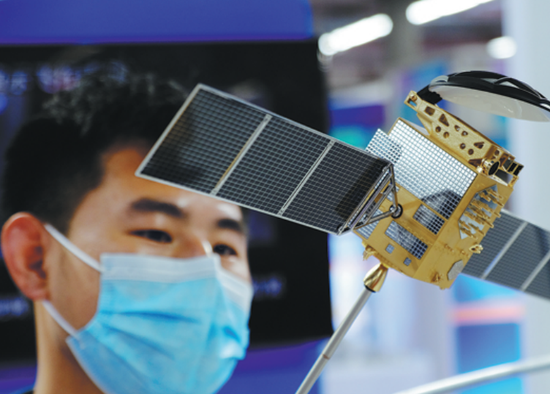 An attendee looks at a model of a Beidou Navigation Satellite at an expo in Shenyang, Liaoning province, in September 2020. (HUANG JINKUN/FOR CHINA DAILY)