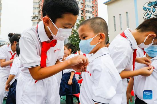 Schools in China ramp up anti-virus measures while welcoming new semester