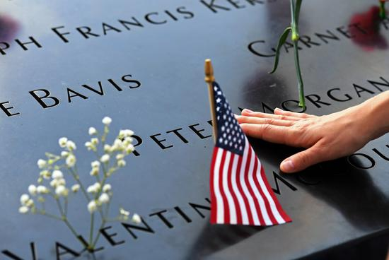 A woman touches a plate on which names of 9/11 victims were inscribed at the National September 11 Memorial and Museum in New York, the United States, Sept. 11, 2019. (Xinhua/Li Rui)