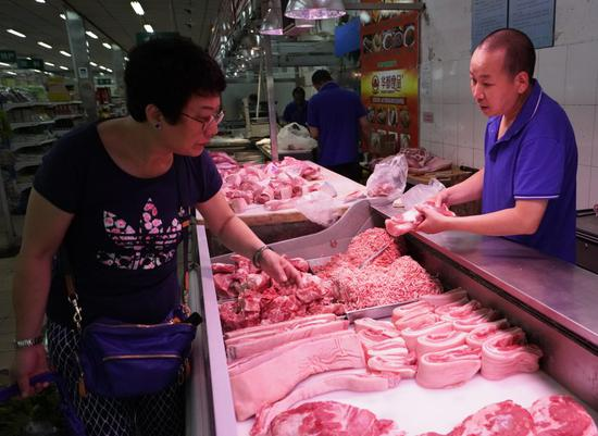 A customer selects meat at a market in Beijing, capital of China, July 10, 2019. (Xinhua/Luo Xiaoguang)