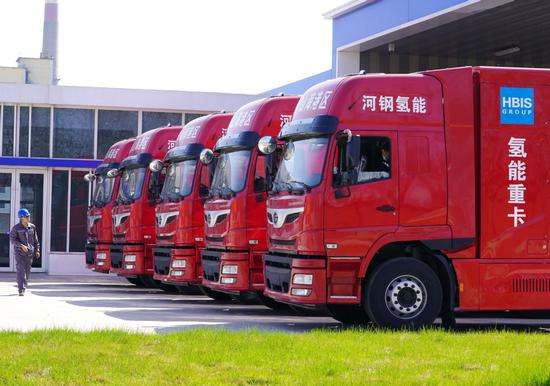 A worker passes a row of hydrogen fuel cell heavy trucks at the Tangshan Port Economic Development Zone in North China's Hebei province in April. (Photo/XINHUA)