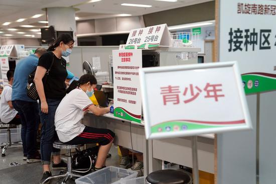 A girl registers before receiving a dose of the COVID-19 vaccine at a vaccination site in Xuhui District of Shanghai, east China, Sept. 3, 2021. (Xinhua/Liu Ying)