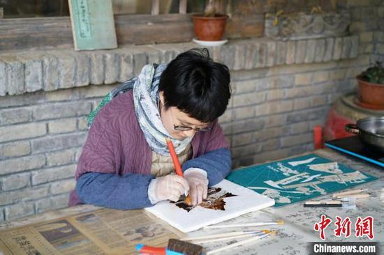 Long Yuyu is carving on a leave on Sept. 12. (Photo/China News Service)