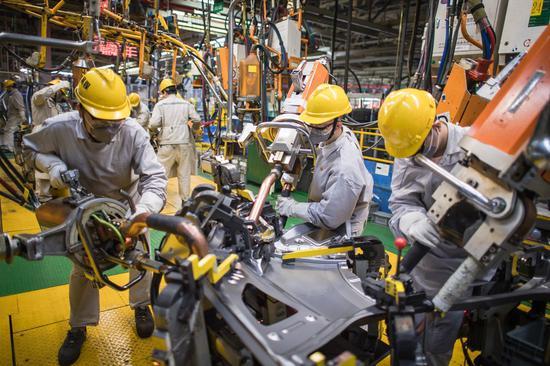 Welder Liu Shigui (2nd R) works at a factory of Dongfeng Motor in Wuhan, capital of central China's Hubei Province, March 30, 2021. (Xinhua/Xiao Yijiu)
