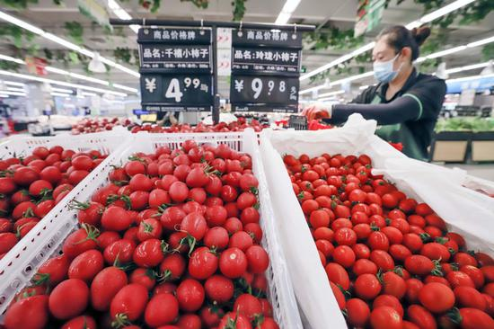A worker arranges fruits in a supermarket in Zunhua, Hebei province on Aug 17, 2021. (Photo/Xinhua)