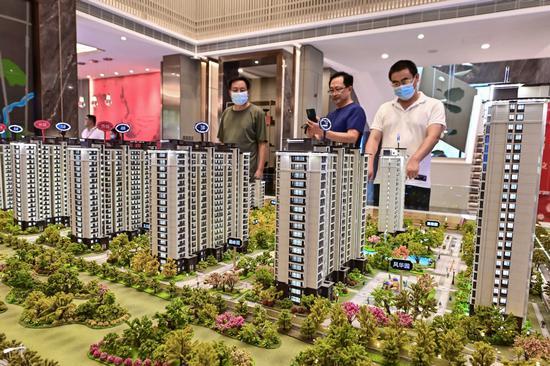 Potential homebuyers look at  property models in Qingdao, Shandong province, on Aug 17, 2021. (Photo: China Daily/Wang Jilin)