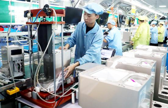 Employees work on the production line of a foreign-funded electronics manufacturer in Suzhou, Jiangsu province. (Photo: China Daily/Hua Xuegen)