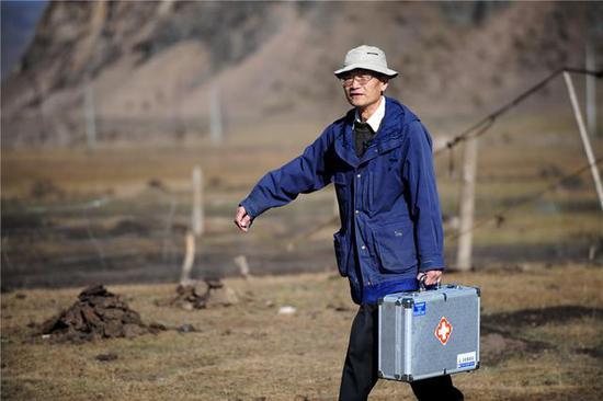 Wang Wanqing walks to treat a patient. (Photo/Xinhua)