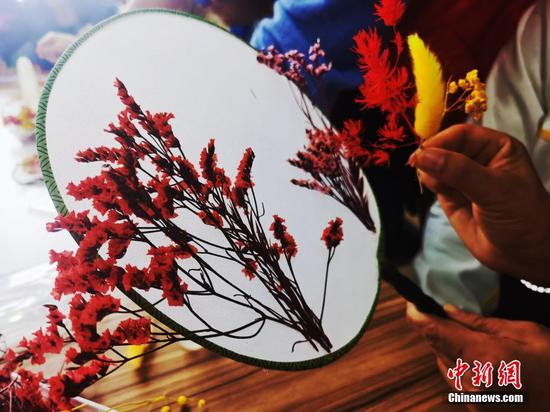 People with disabilities make traditional moon-shaped fans symbolizing reunion in Qinghai