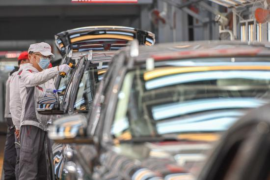 Workers check vehicles at the general assembly line of Hongqi, the leading sedan brand of First Automotive Works (FAW) Group Co. Ltd., in Changchun, Northeast China's Jilin province, Sept 23, 2020. (Photo/Xinhua)