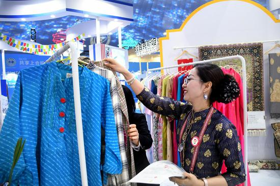 An exhibitor introduces products to a guest during the 2021 Shanghai Cooperation Organization (SCO) International Investment and Trade Expo in Qingdao, east China's Shandong Province, April 26, 2021.(Xinhua/Li Ziheng)