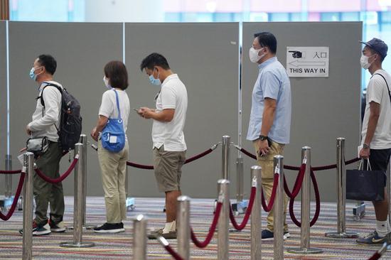 People queue to cast their ballots at a polling station at Hong Kong Convention and Exhibition Center in Hong Kong, south China, Sept. 19, 2021. (Xinhua/Wang Shen)