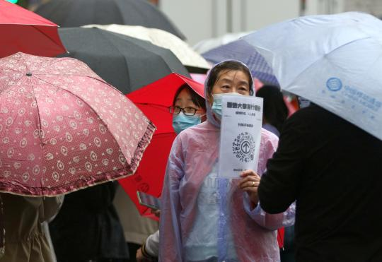 A community worker holds a QR code in the rain to check on the travel information of people waiting for COVID-19 nucleic acid tests in Harbin, Heilongjiang province, on Wednesday. (Photo/CHINA DAILY)