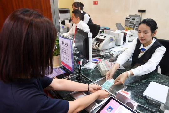 A staff member (right) hands over a stack of renminbi banknotes to a customer at an Industrial and Commercial Bank of China branch in Beijing, on Aug 30, 2019. (Photo/Xinhua)