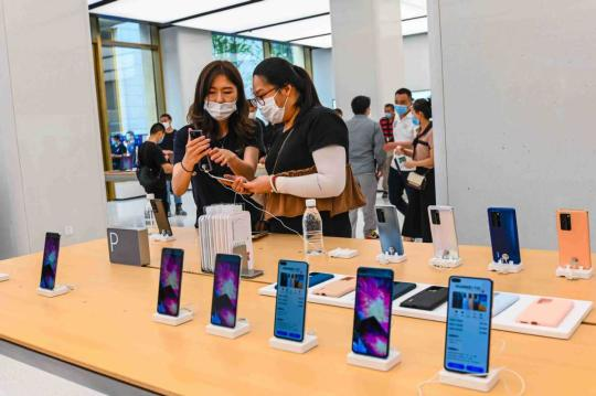 Shoppers check smartphones at a store in Shanghai. (Photo/China Daily)