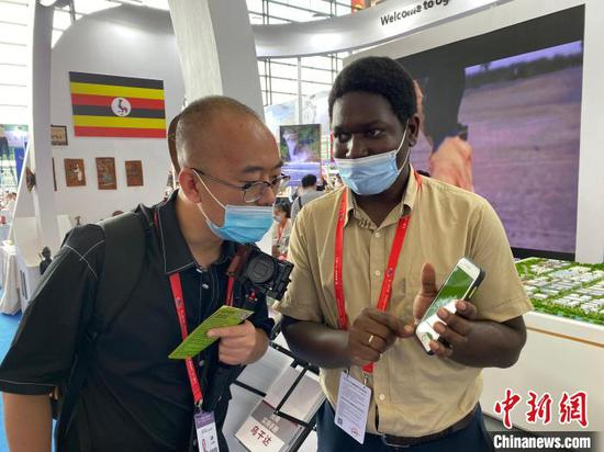 Ugandan business man Ssonko Wilson (R) introduces products at the second China-Africa Economic and Trade Expo in Changsha, capital of Hunan Province, Sept. 29, 2021. (Photo/China News Service)