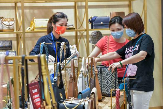 Customers purchase bags at a duty-free shop in Haikou, Hainan province, on Oct 1, 2021. [Photo/IC]