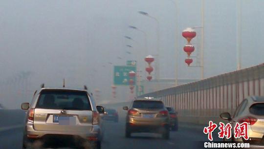 乌鲁木齐苏州路高架桥两旁楼宇在雾气中若隐若现。 王小军 摄