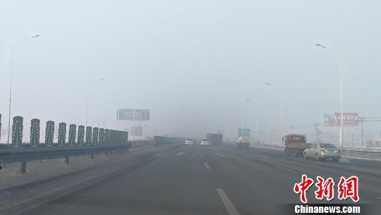 """乌鲁木齐至昌吉快速路两旁楼宇""""消失""""在雾气中。 王小军 摄"""