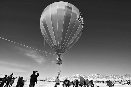 2月3日,游客在赛里木湖景区体验热气球升空,领略冰雪风情。