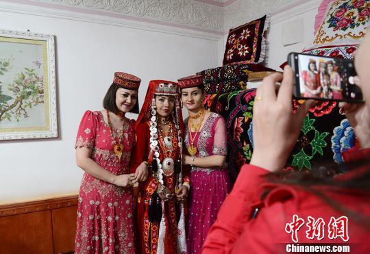 婚礼仪式开始前,人们都争相和美丽的新娘合影留念。 勉征 摄