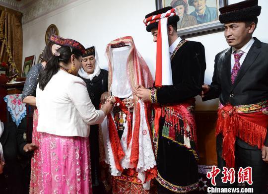 新郎新娘在婚礼仪式上交换系着红白两色手绢的戒指。 勉征 摄